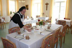 Gästeschwester beim Tische eindecken