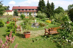 Klostergarten mit Gartenteich und im Hintergrund das Schwesternhaus
